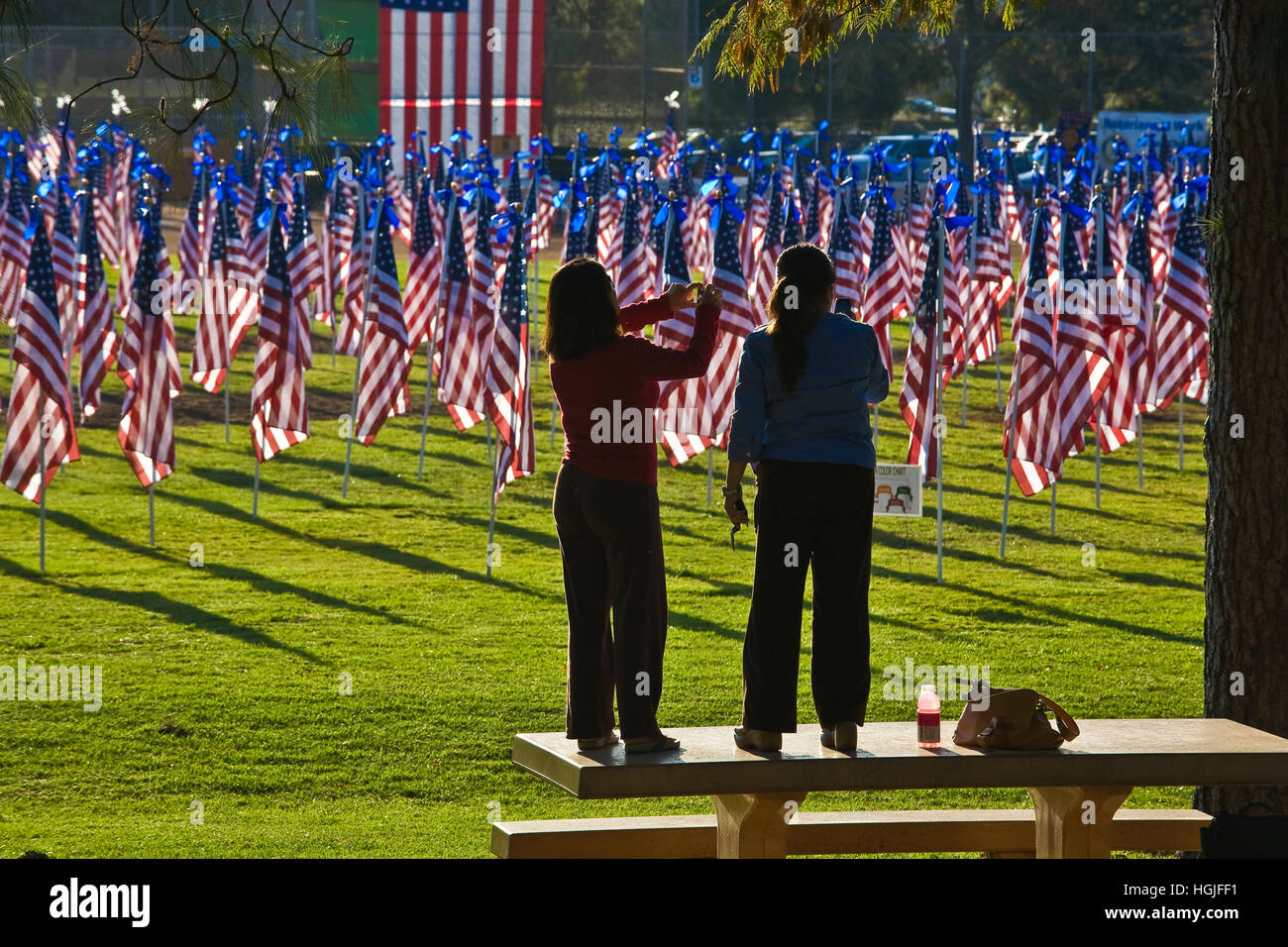 Two women stand on picinc table to take cell phone photo of the Rancho Bernardo Healing Field, created with 1,100 - Stock Image