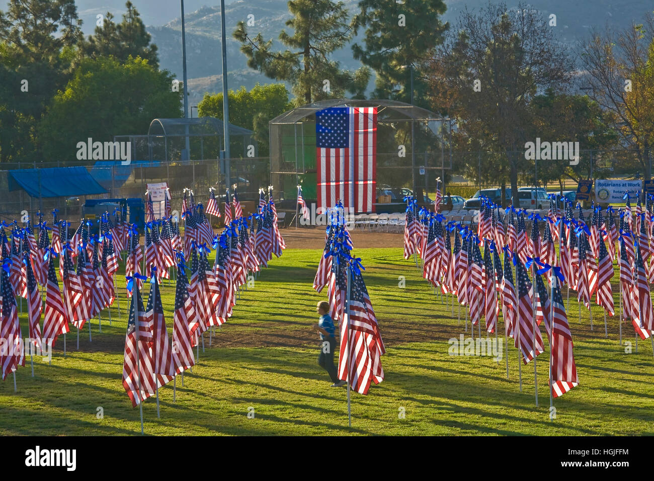 Boy runs through the Rancho Bernardo Healing Field, created with 1,100 3-foot-by-5-foot American flags on 8-foot - Stock Image