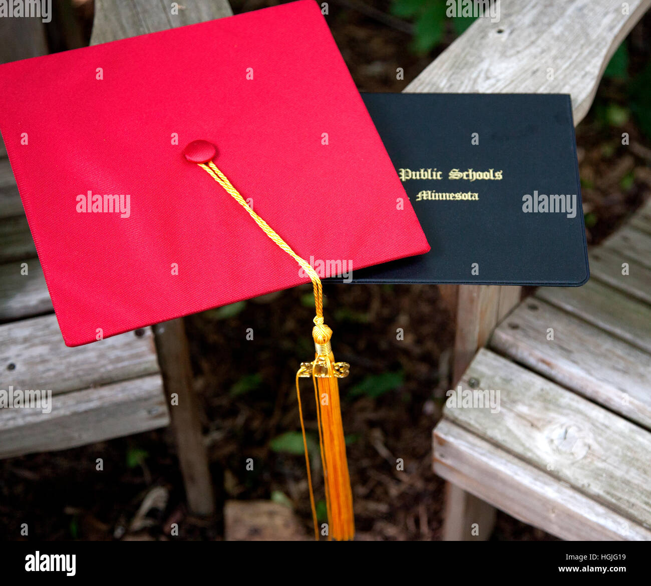 High school graduates red cap with gold tassel and diploma folder displayed at graduation party. St Paul Minnesota - Stock Image
