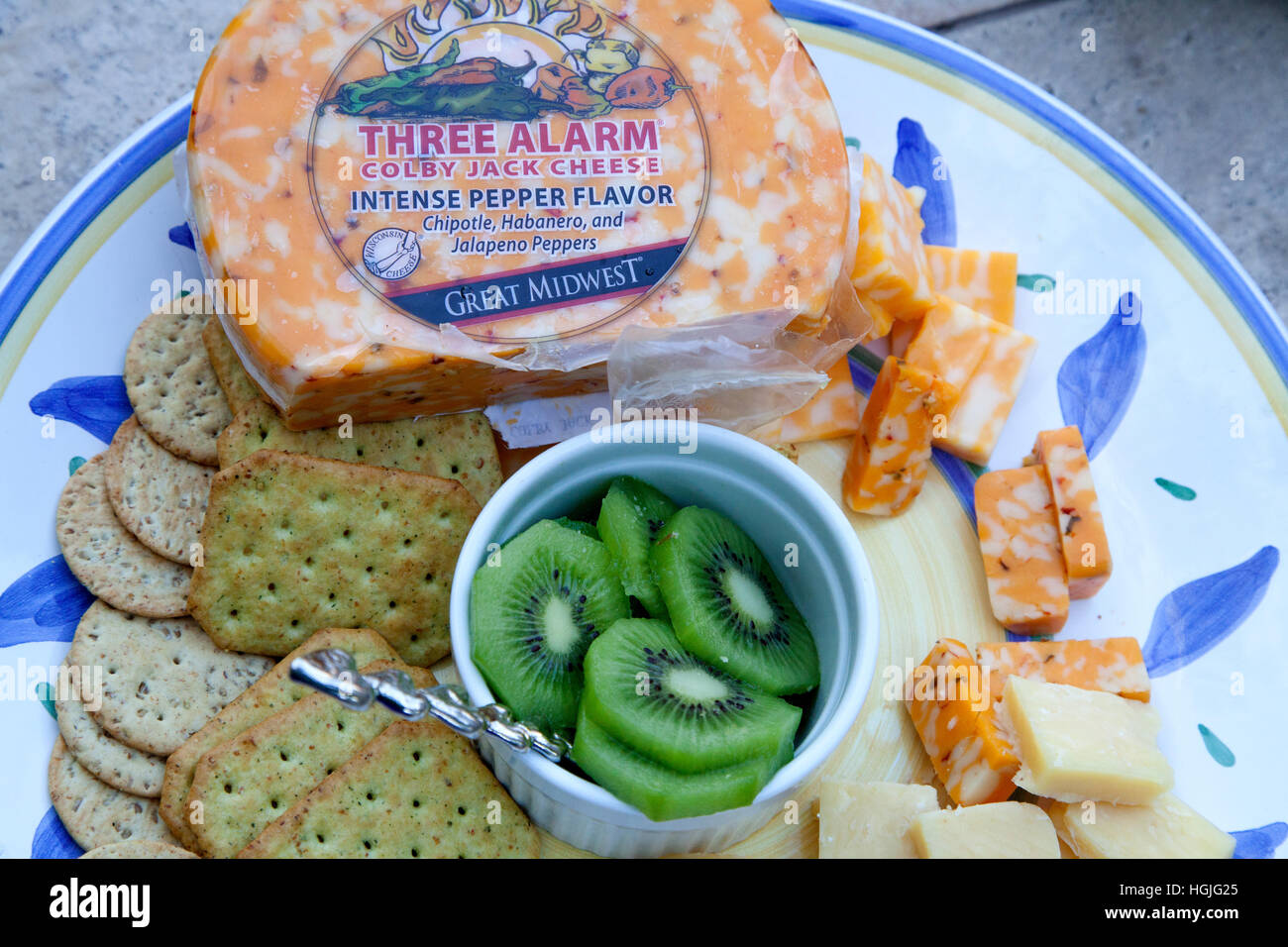 Snack tray with sliced kiwi fruit surrounded by crackers and Three Alarm intense pepper cheese. St Paul Minnesota - Stock Image