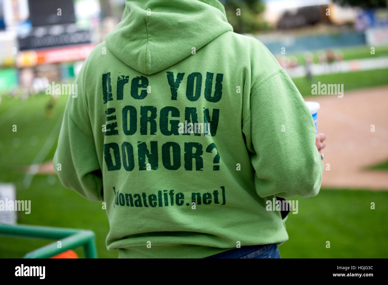 Man wearing green sweatshirt with 'Are you an organ donor?' on the back with donatelife URL address. St - Stock Image