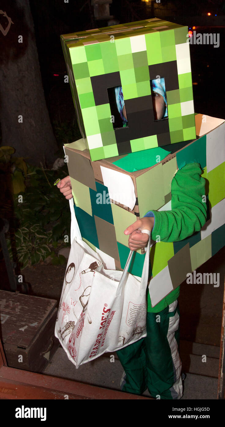 Halloween 'Minecraft' costumes The Box Robot Revisited worn by trick or treater with large candy sack. St - Stock Image