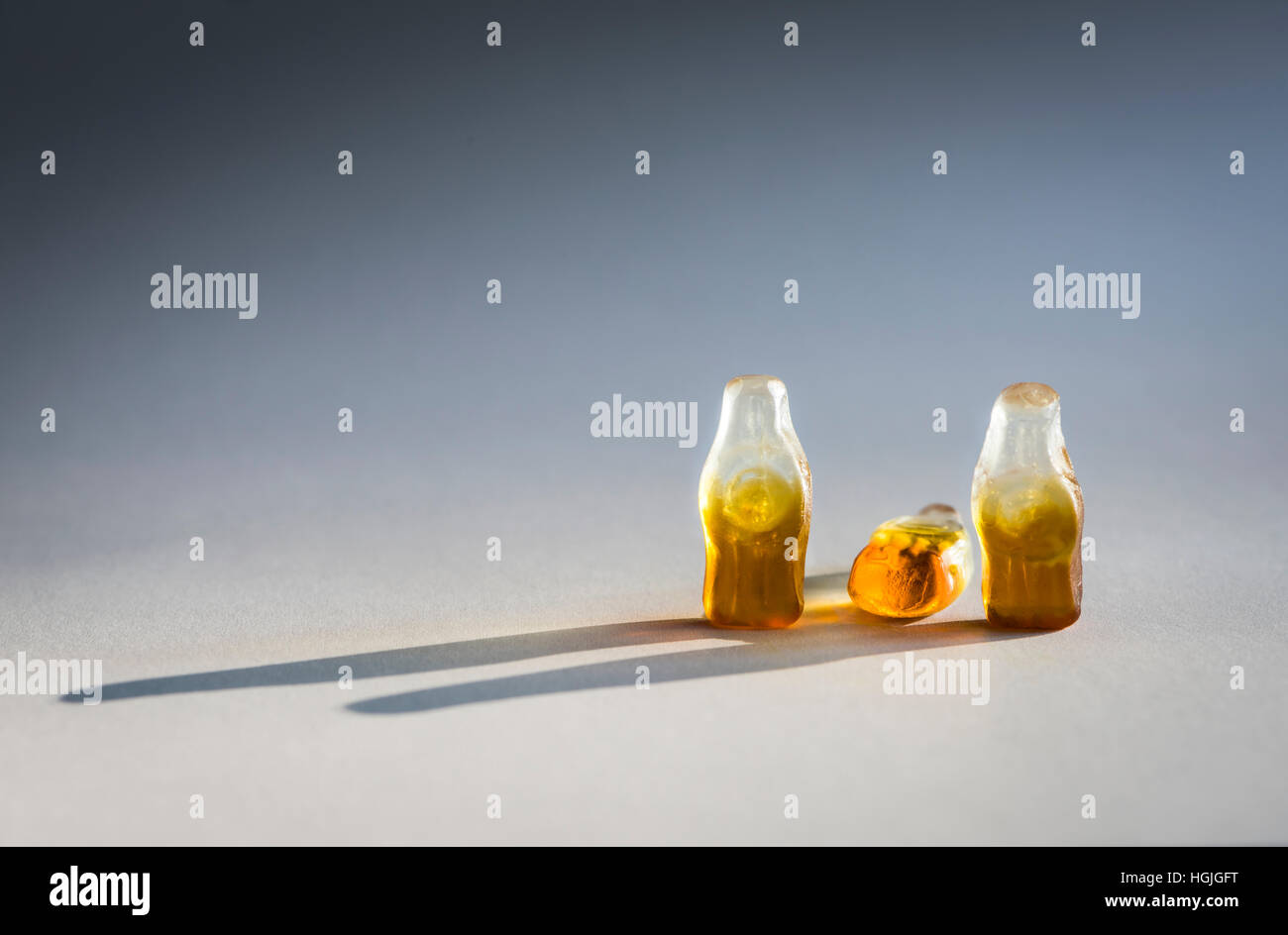 Group of three soft candy / jelly beans in the shape of bottles. Looks like group of three people. Middle bottle Stock Photo