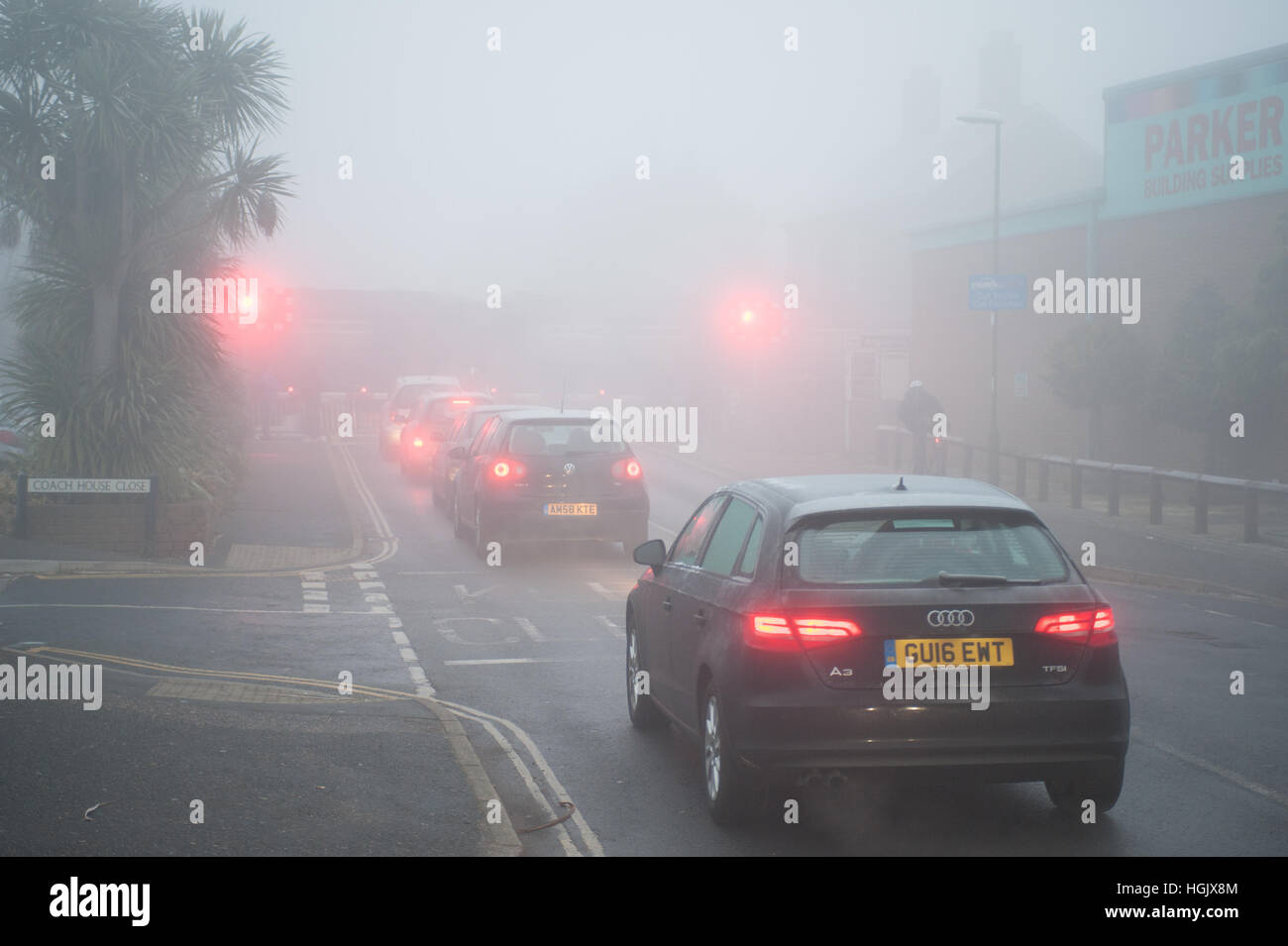 On a foggy morning queuing cars wait in a line of traffic at a railway level crossing in West Sussex, England, UK. - Stock Photo