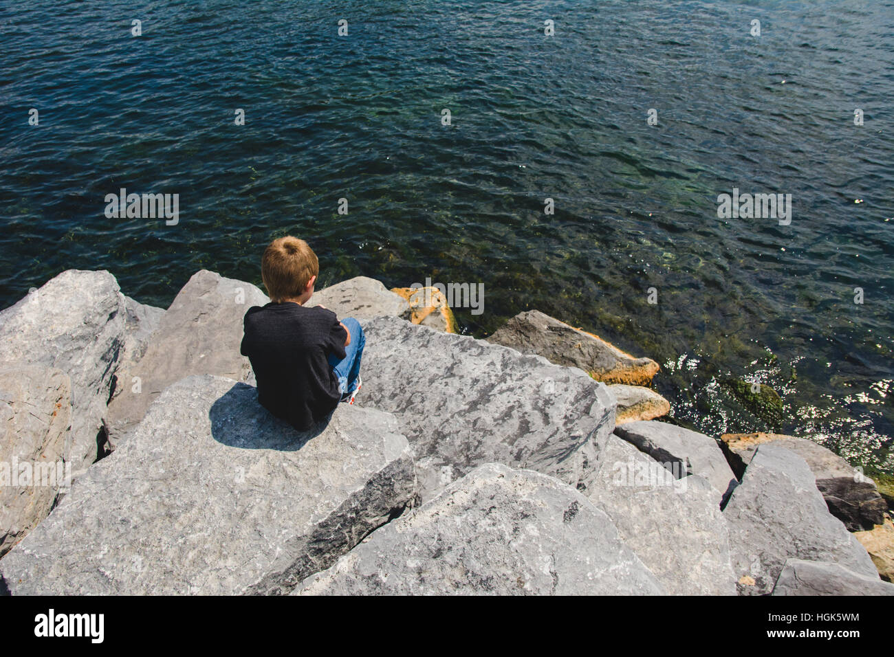 A boy sits on a rock at a lake in the Finger Lakes region of NY - Stock Image