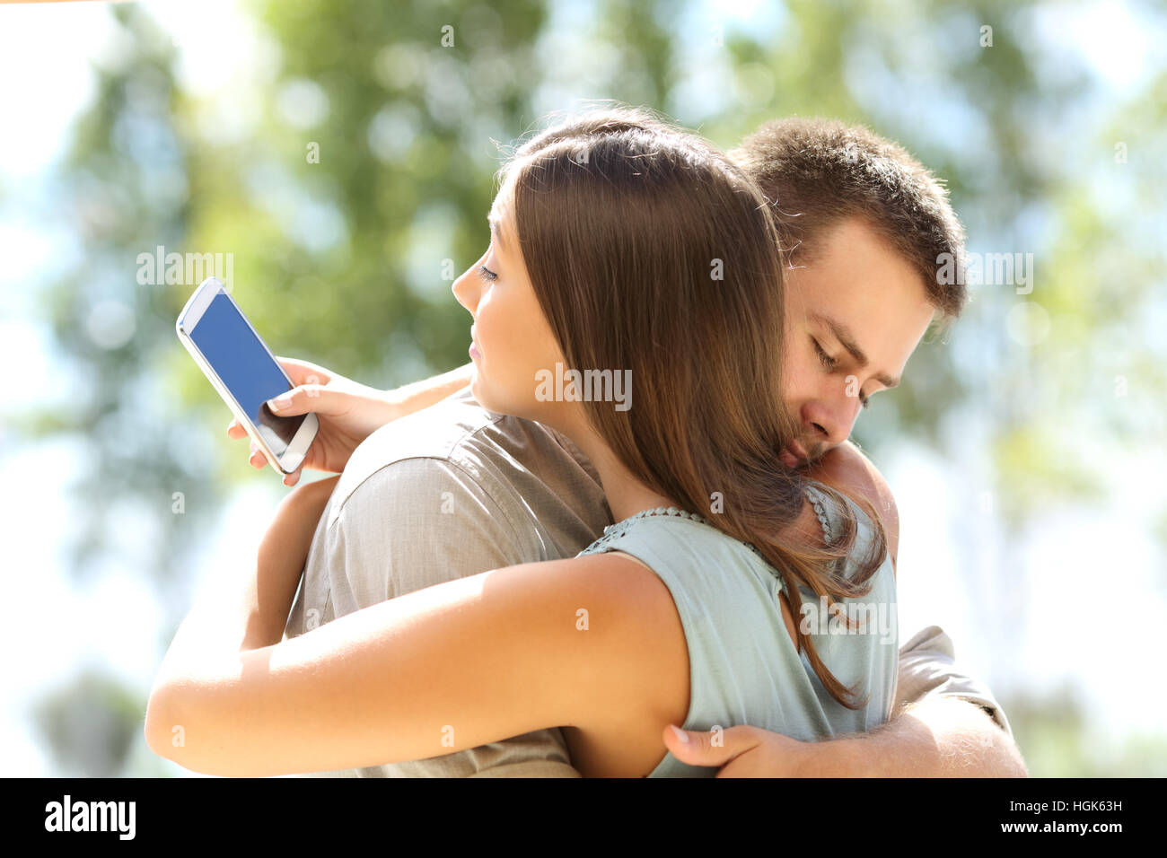 Girlfriend cheating texting on the phone and hugging her innocent boyfriend - Stock Image