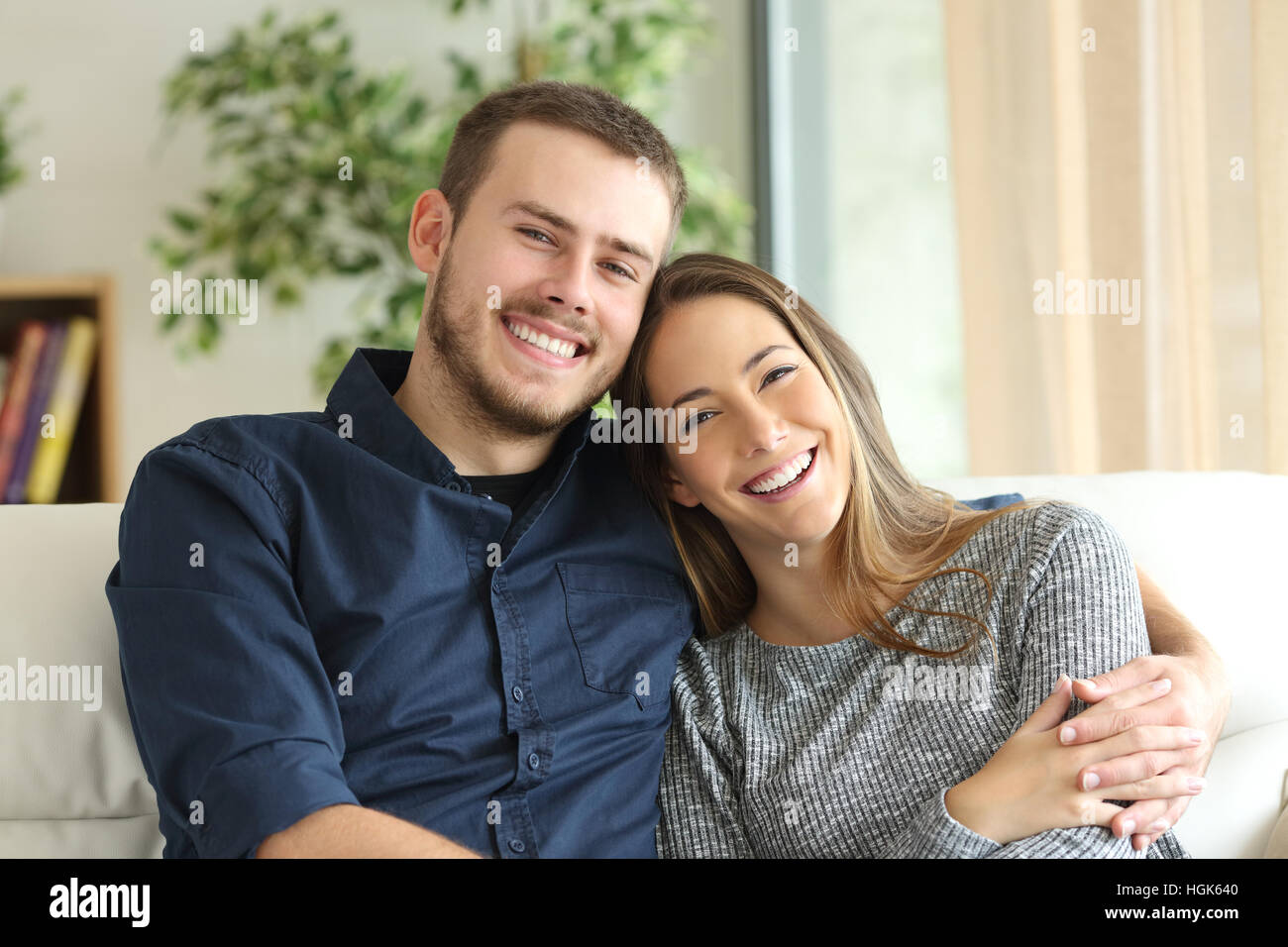 Front view portrait of a happy couple posing and looking at camera sitting on a couch in the living room at home - Stock Image