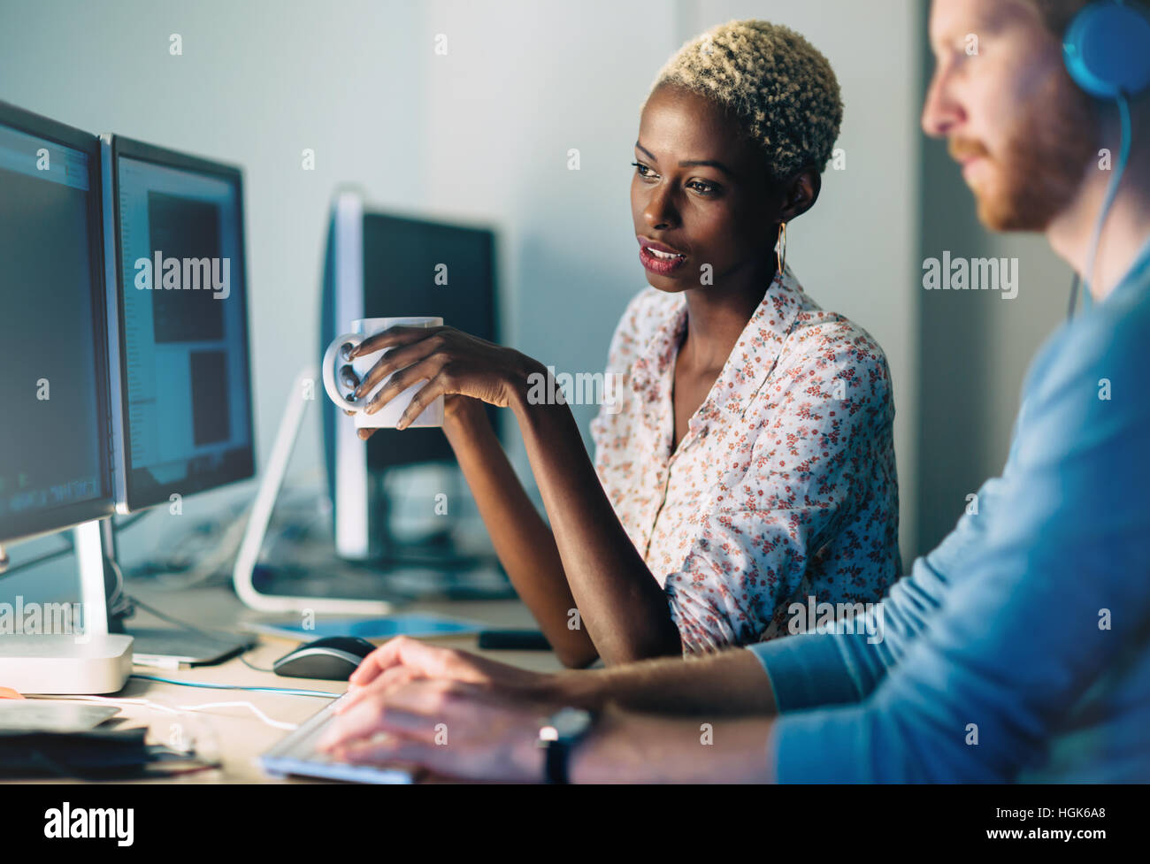 Programmers cooperating at  IT company developing apps - Stock Image