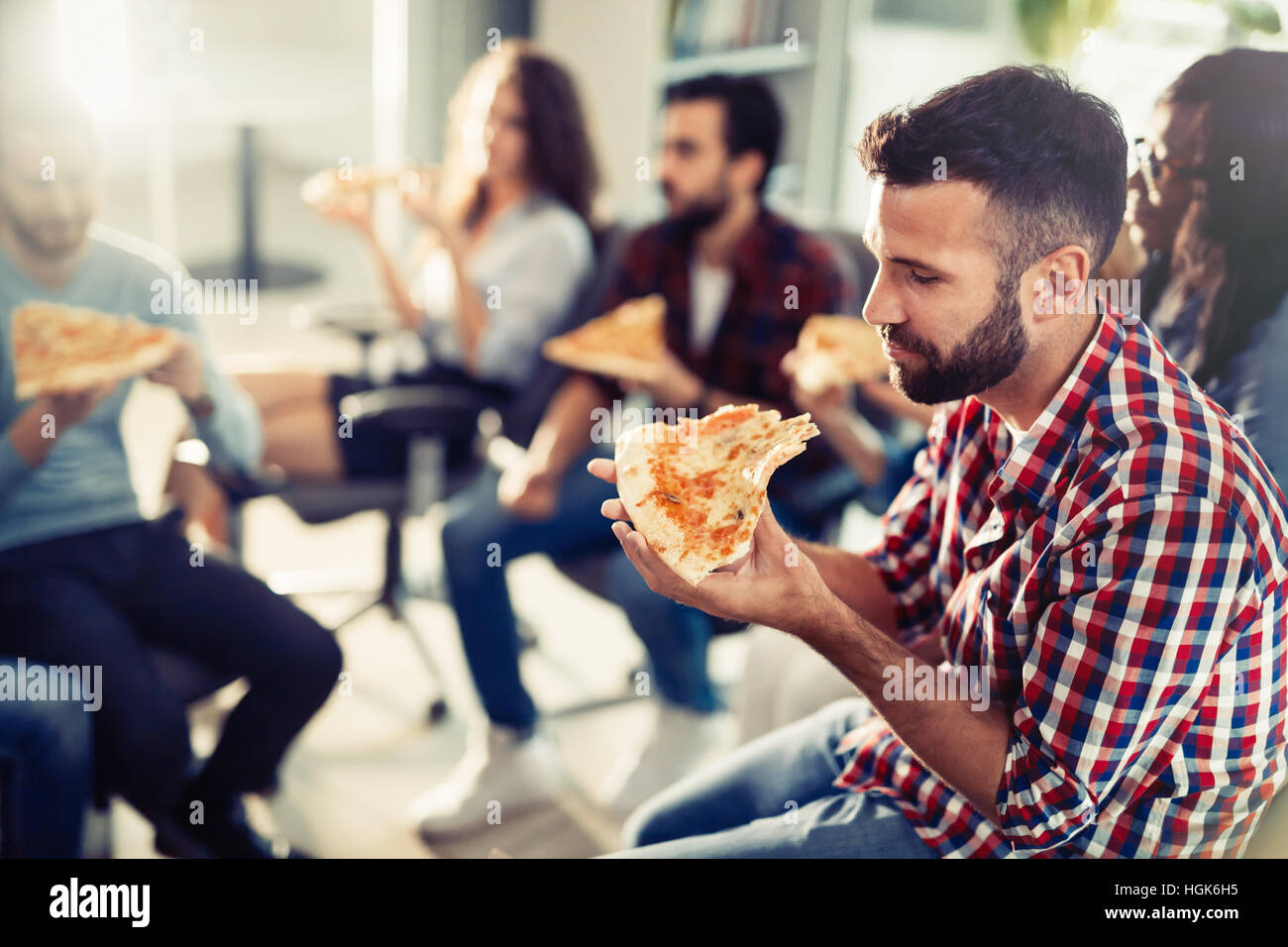 Coworkers eating pizza during work  break at office Stock Photo