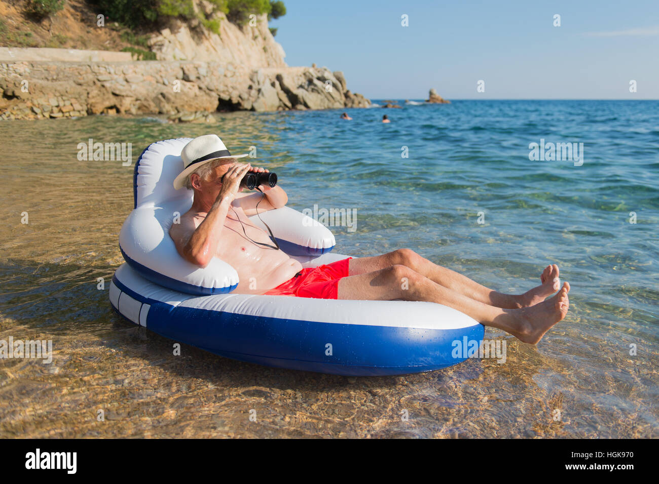 Senior man with spy glasses floating on chair in the sea - Stock Image
