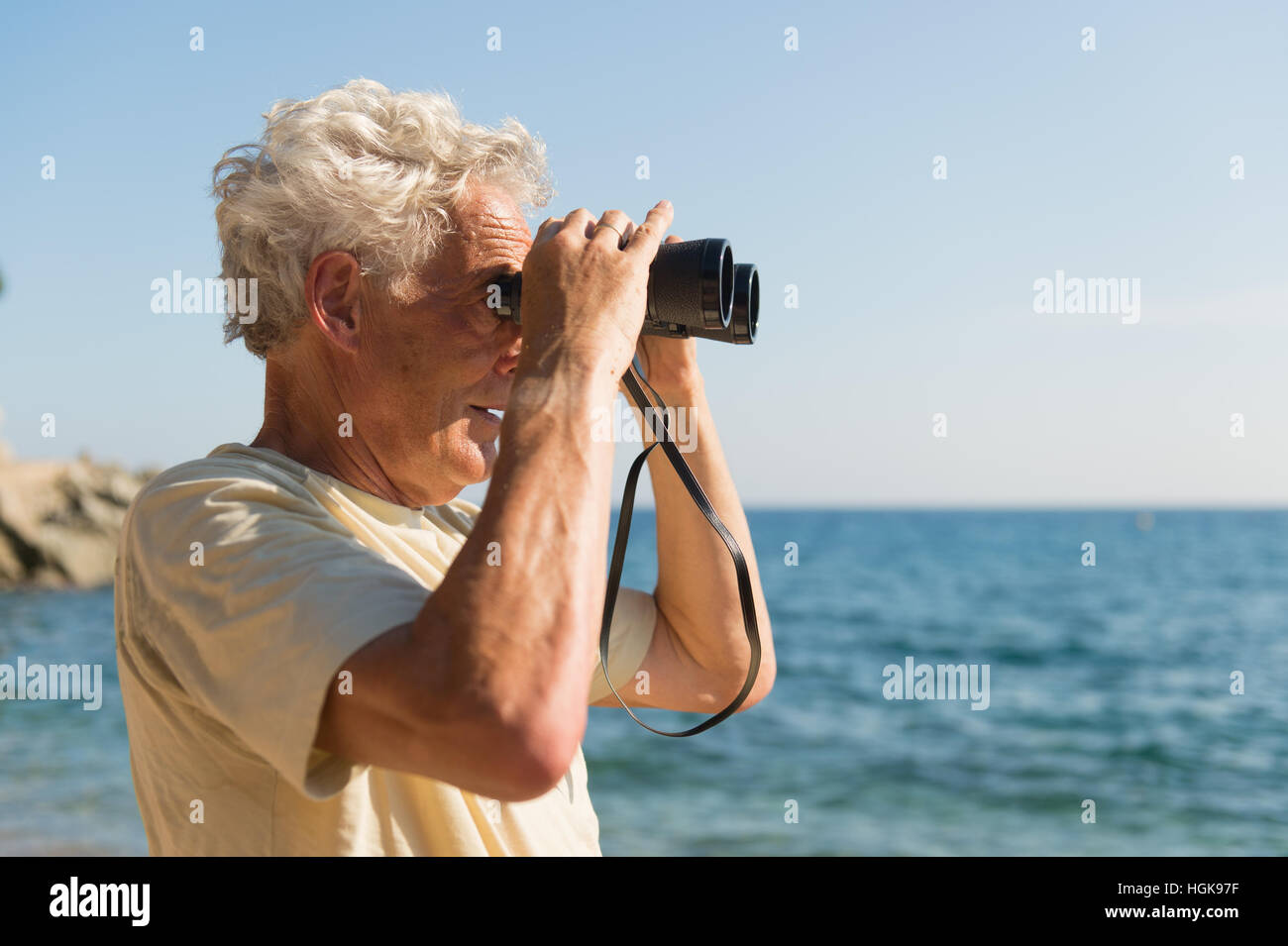Senior man with spy glasses at the beach - Stock Image