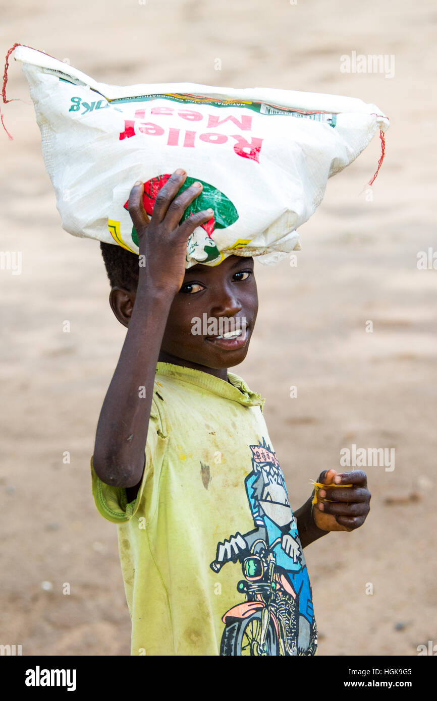 Local boy balancing a bundle, Livingstone, Zambia - Stock Image