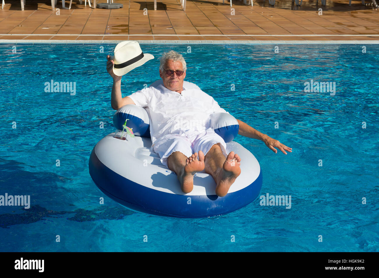 wealthy man relaxing in own swimming pool - Stock Image