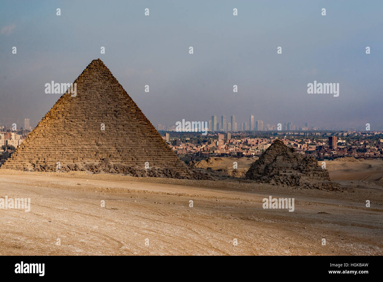 The smallest of the pyramids in Giza is in ruins but its neighbor is still intact and the city of Cairo is in the - Stock Image