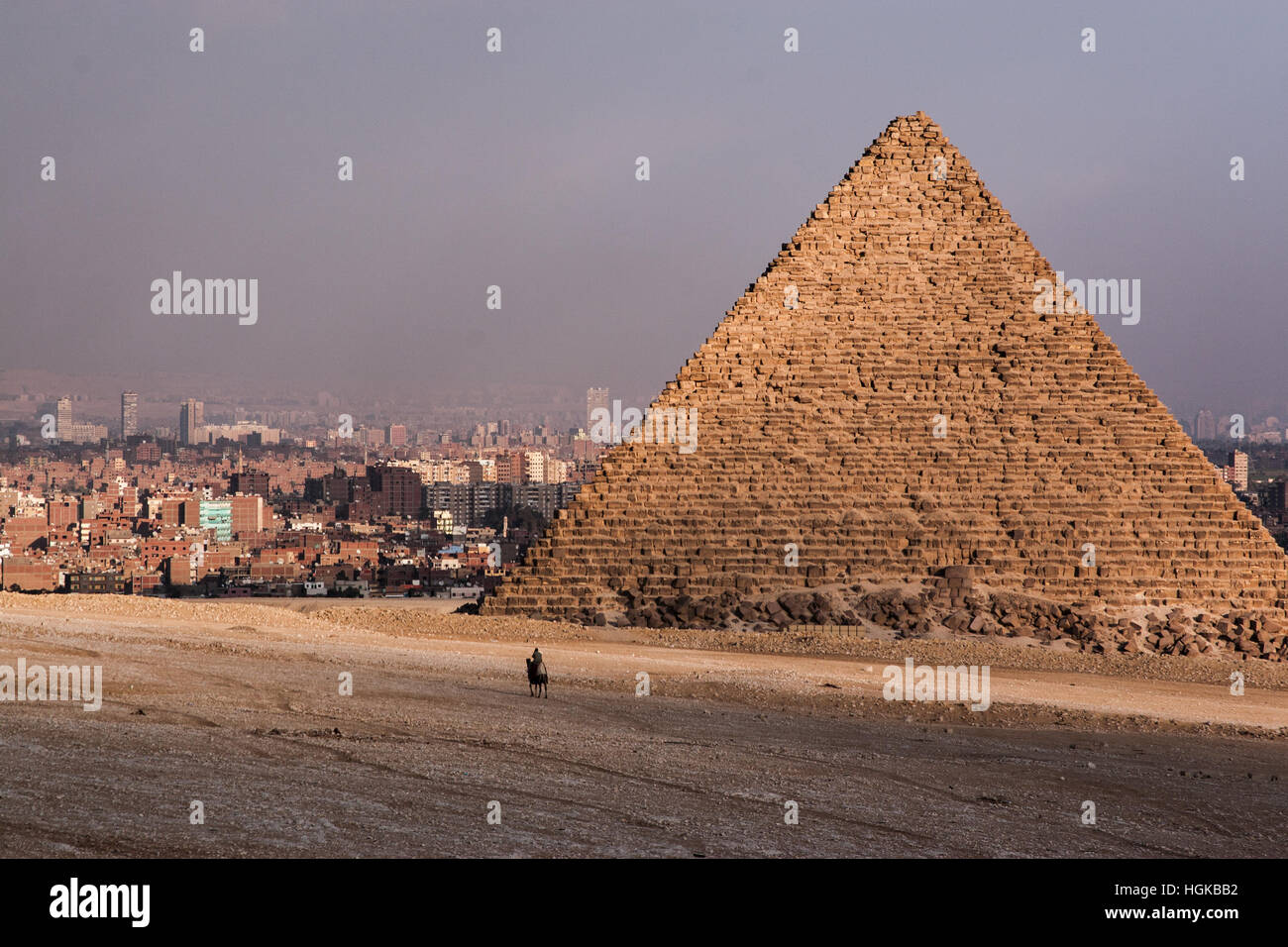 Lone rider on a camel near the base of one of the pyramids of Giza with the city of Cairo in the background. - Stock Image