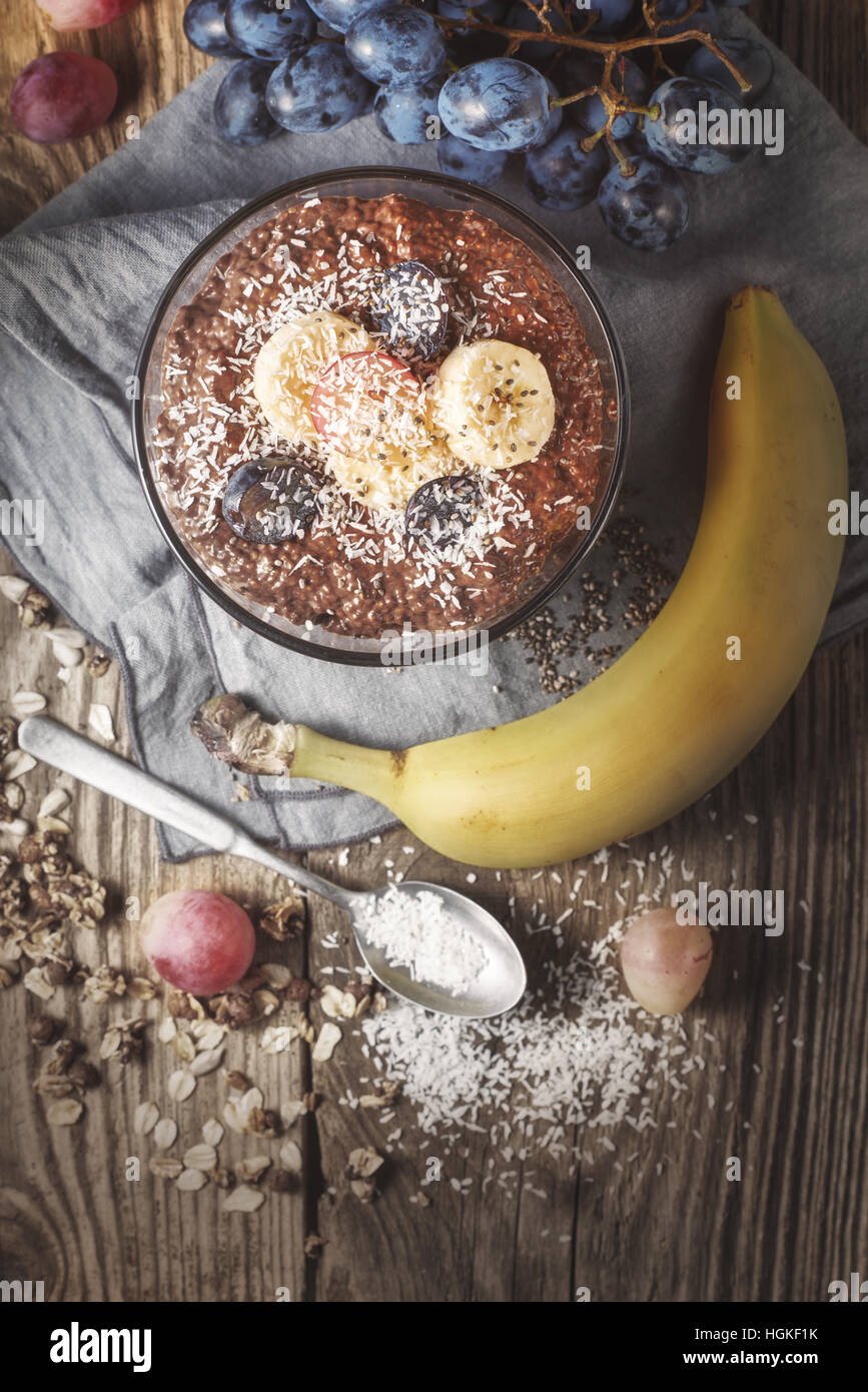 Chocolate chia pudding with fruits on the wooden table  top view - Stock Image