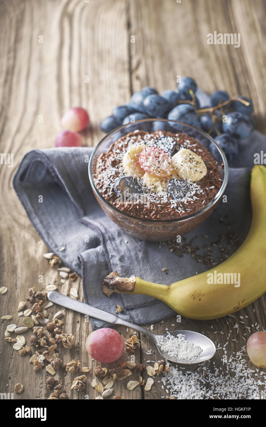 Chocolate chia pudding with fruit in the glass bowl vertical - Stock Image