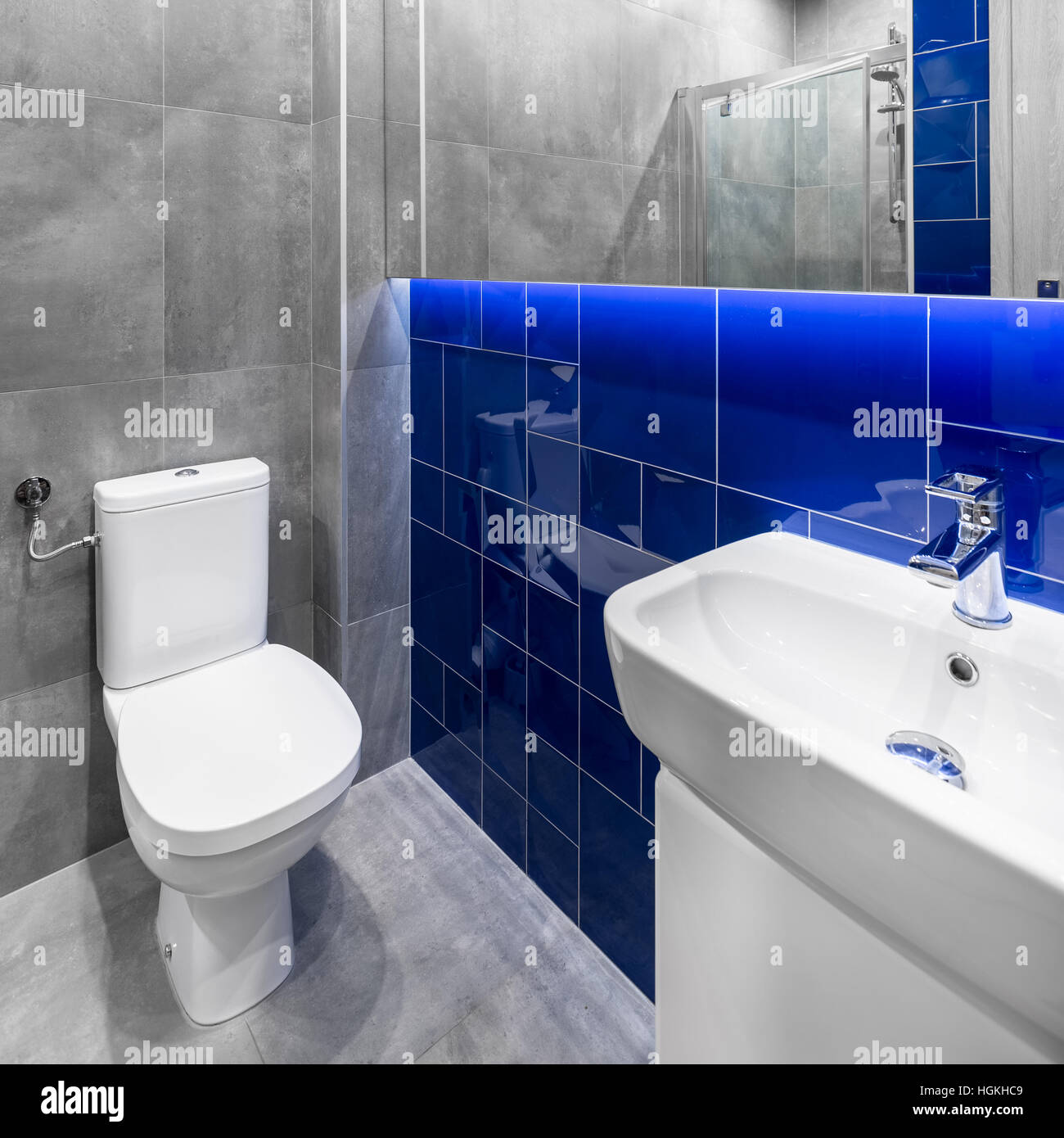Small bathroom in grey and blue with toilet, sink and basin cabinet ...