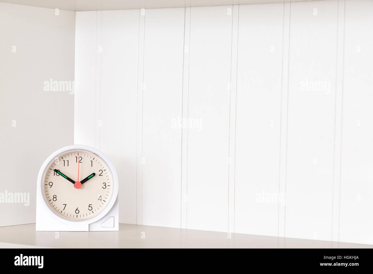 A clock sits on an empty shelf with plenty of white copy space behind it. - Stock Image