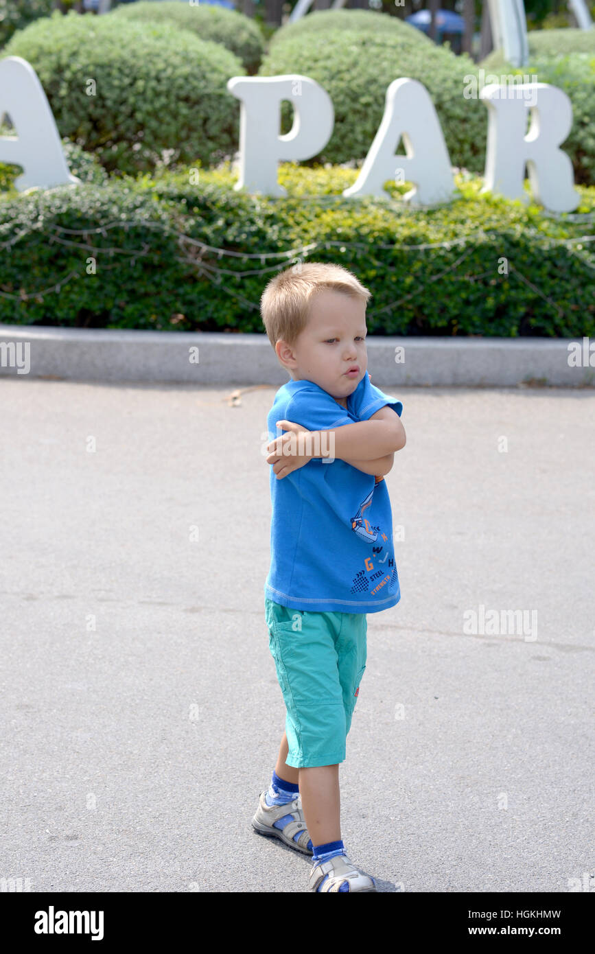 hurt and crying child goes through the park - Stock Image