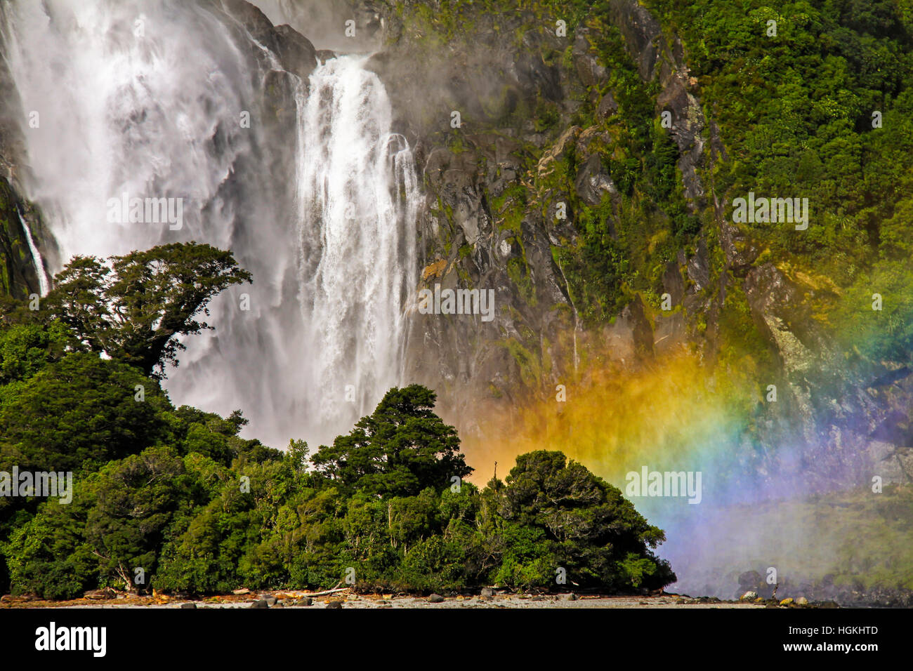 Lush Rainforest and Thundering Bowen Waterfall Landscape at Mouth of Milford Sound in Fiordland National Park, New - Stock Image