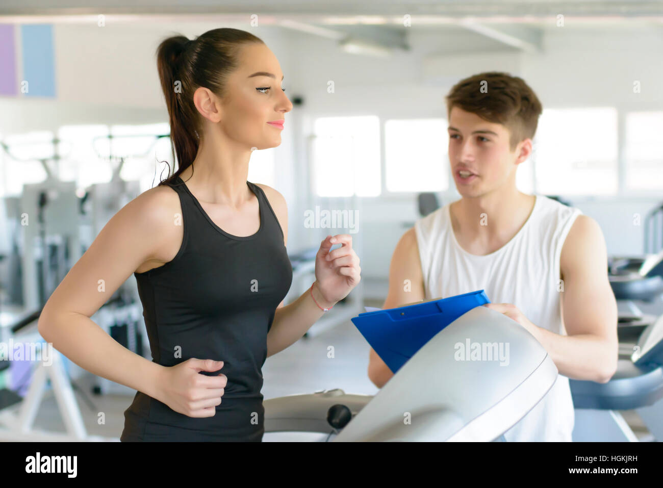 Woman running on treadmill at gym and being assisted by personal trainer - Stock Image