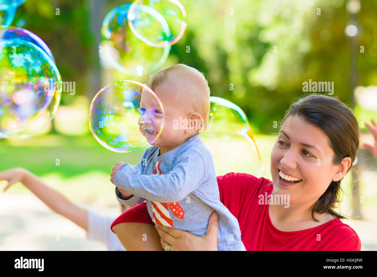 Cute baby and his mother catching soap bubbles in a summer day - Stock Image
