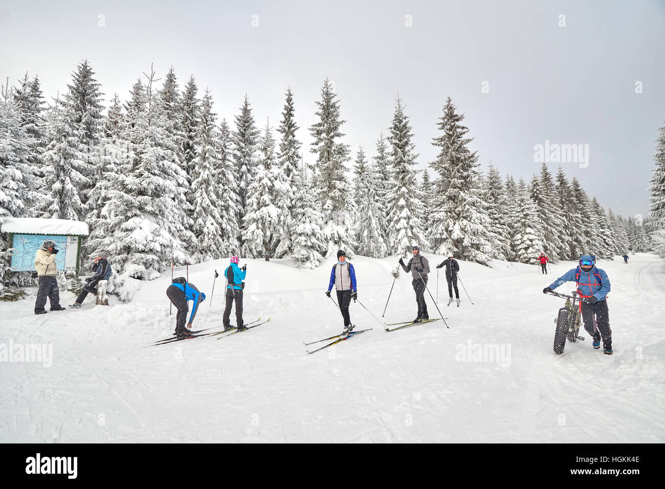 Winter sports enthusiasts resting on trails intersection. - Stock Image