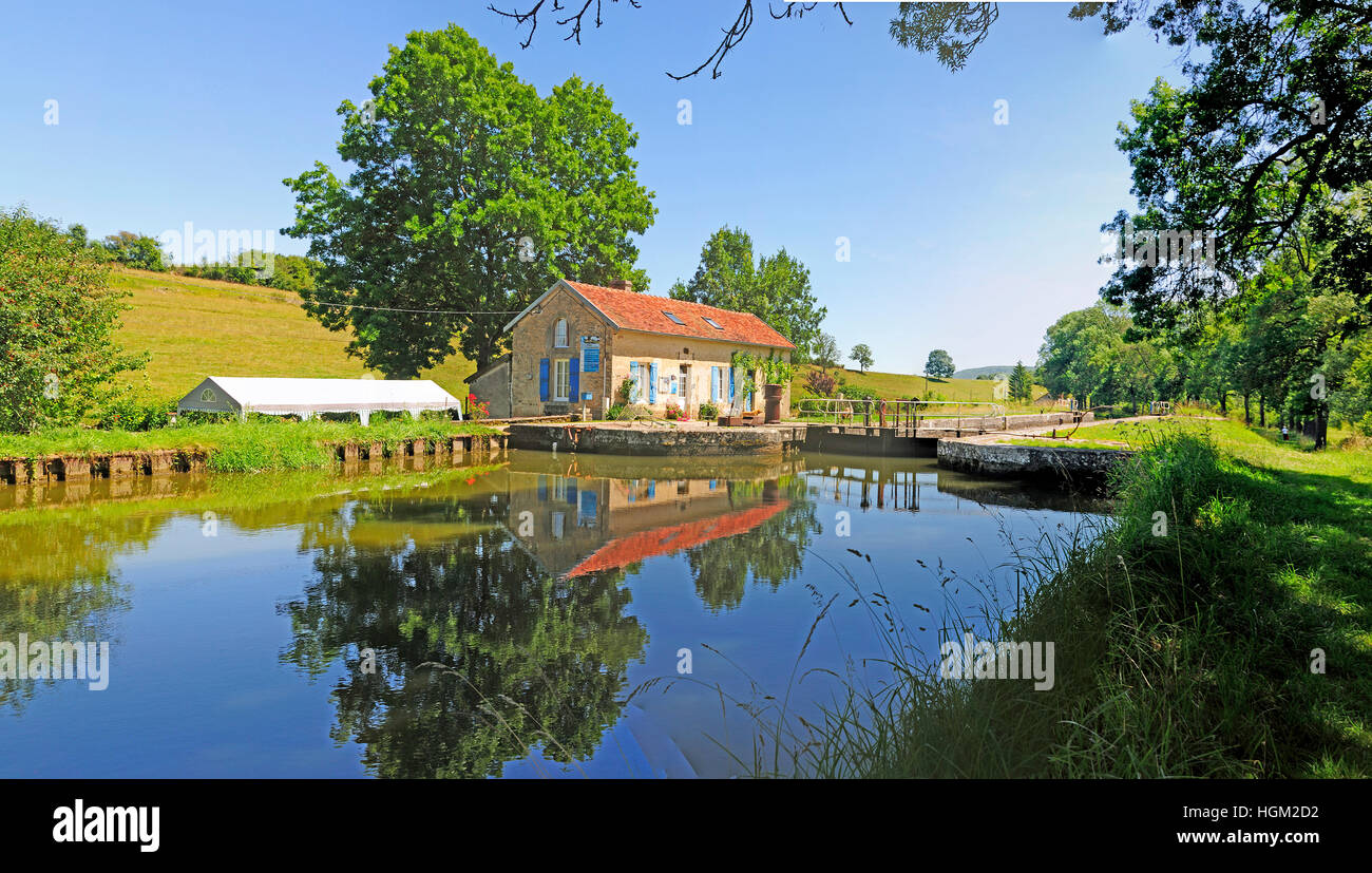 Lock on the Dijon canal in Burgundy with reflection of lock house in the canal. Stock Photo