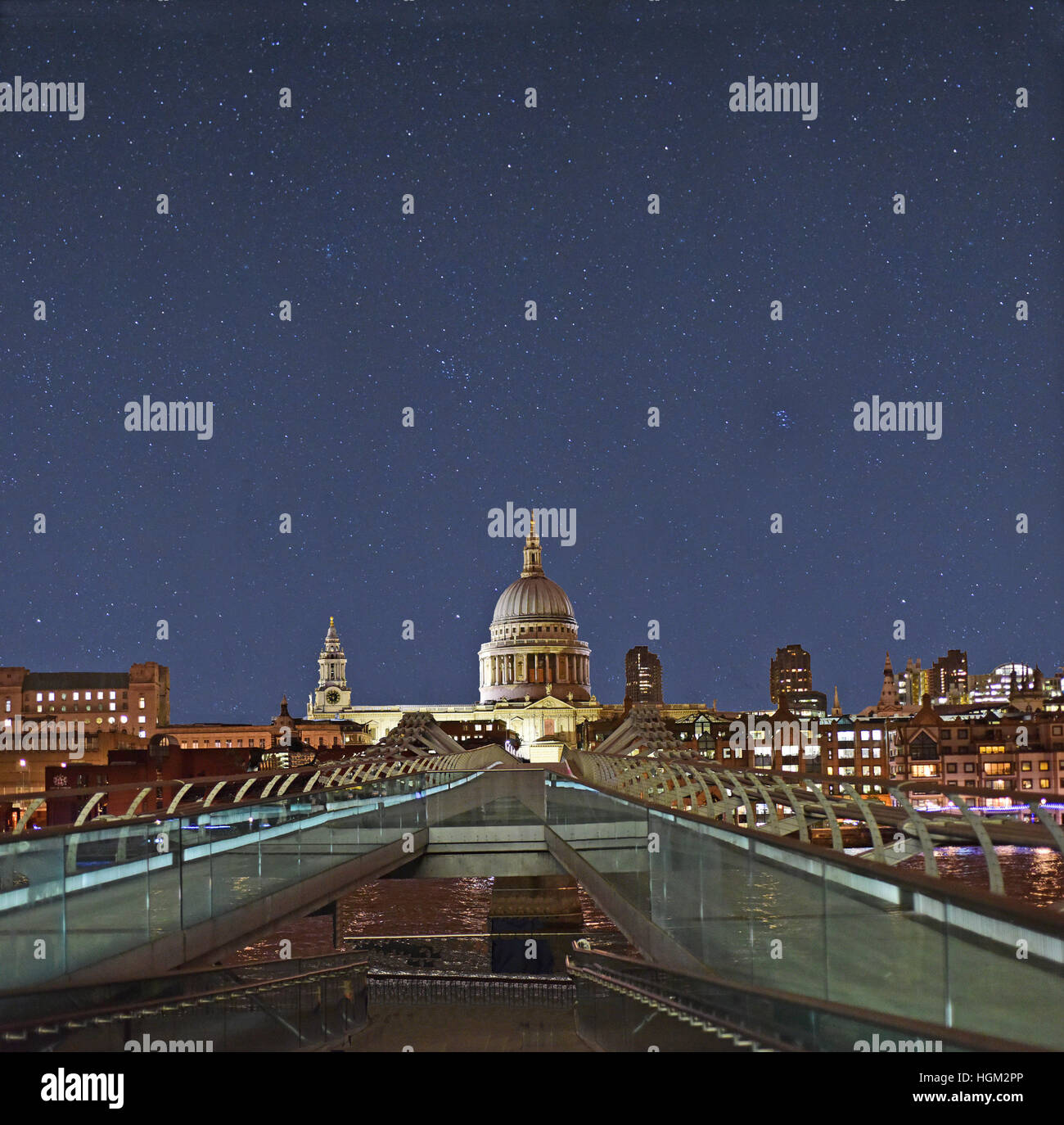 The Millennium Bridge and the Great Dome of St. Paul's cathedral in London against a clear night sky. - Stock Image