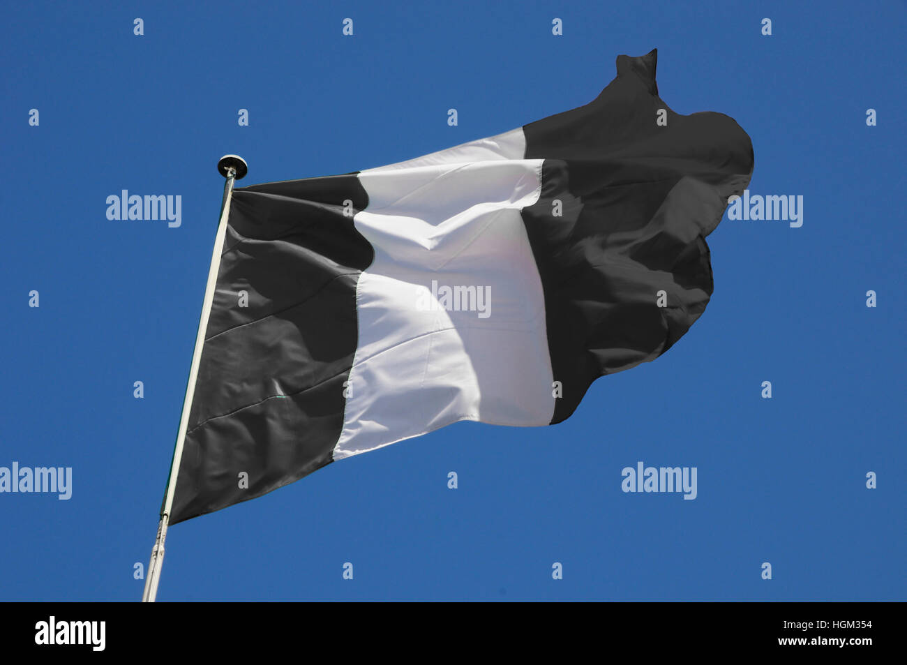 Black and White striped flag fluttering in a brisk breeze against a bright blue sky. - Stock Image