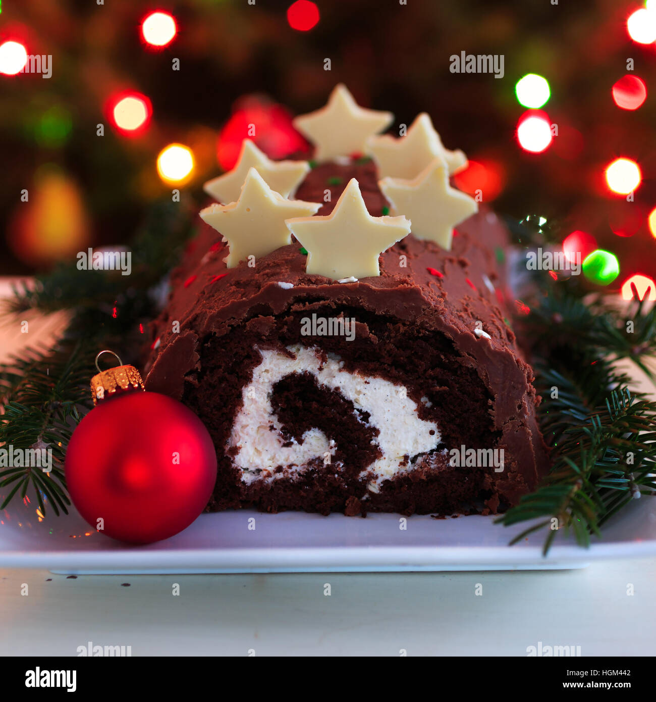 Homemade chocolate yule log Christmas cake against a background of Christmas lights. - Stock Image
