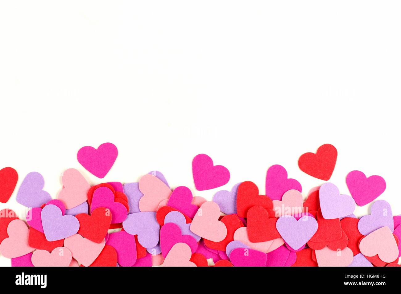 Valentines Day border of colorful paper hearts over white - Stock Image