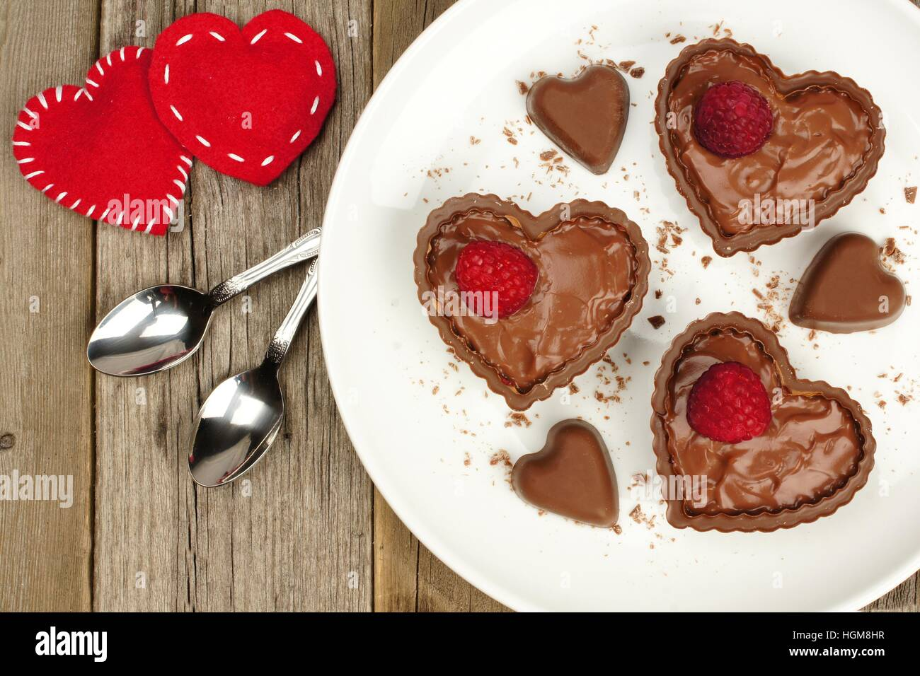 Heart shaped chocolate dessert cups with pudding and raspberries on plate with wood background - Stock Image