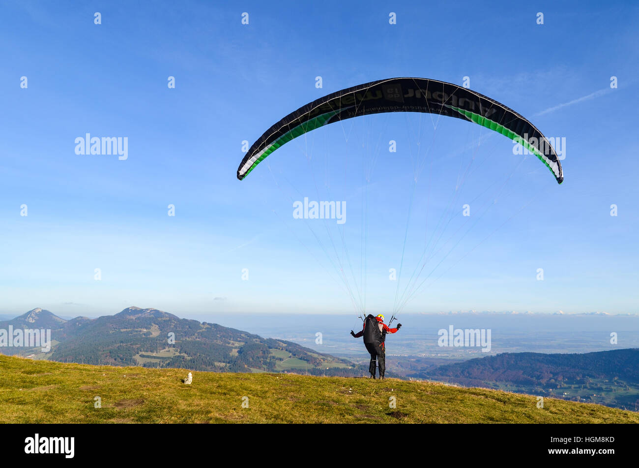 Paraglider taking off from Mont d'Or in France and flying over the Jura mountains Stock Photo