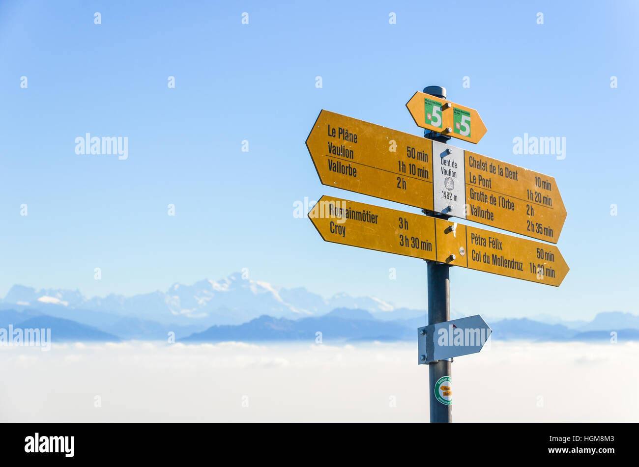 Hiking signs and panorama of the Swiss Alps seen from the Dent de Vaulion in the Jura, including Mont Blanc - Stock Image