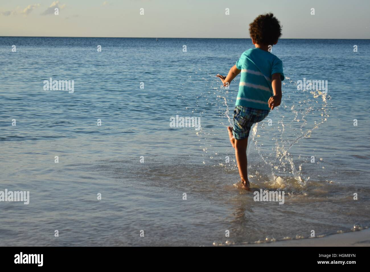 Boy playing in the waves Stock Photo
