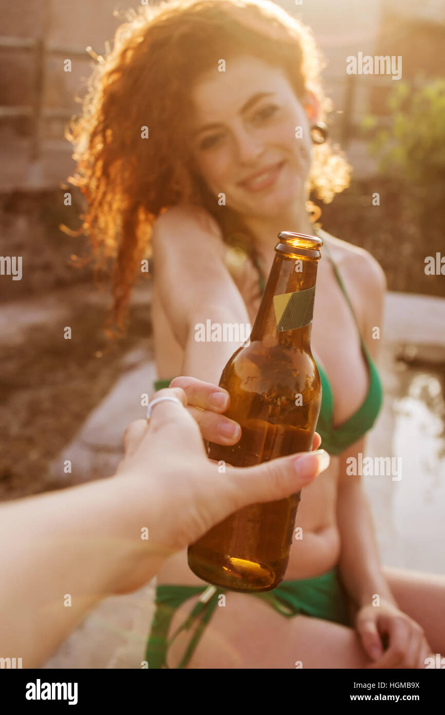 Young redhead woman at a summer party with a beer bottle - Stock Image