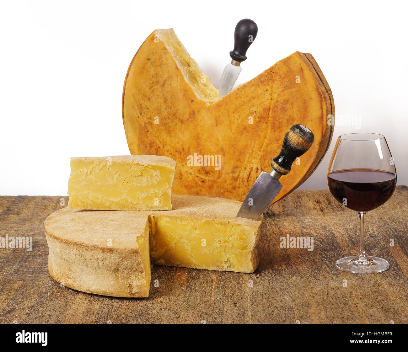 Old cheeses with wine on wood table - Stock Image