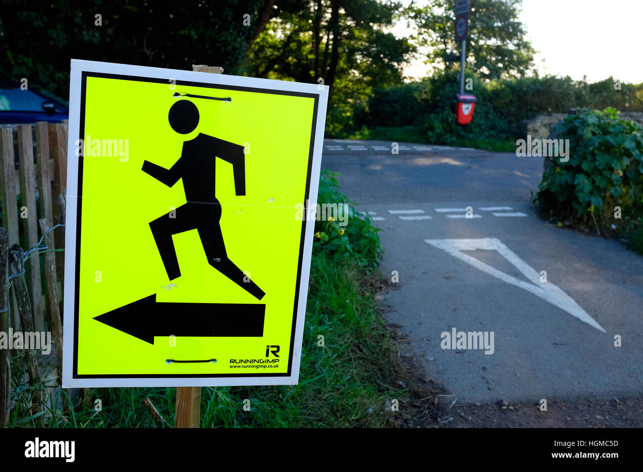 running triathlon road race this way man graphic sign rural road to the left move run sprint jog jogging arrow silhouette - Stock Image