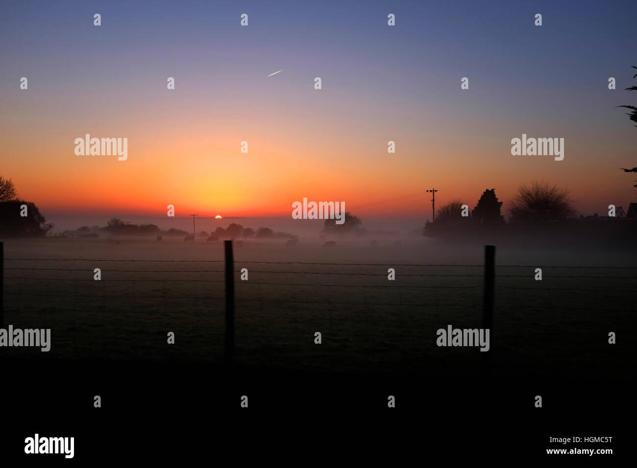 sunset across misty field with fence autumn frosty trees Northwood Isle of Wight England UK - Stock Image
