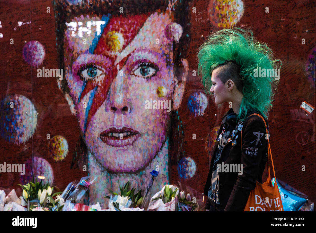 London, UK. 10th January, 2017.  A girl with a green mohican haircut pays tribute to David Bowie in front of a mural - Stock Image