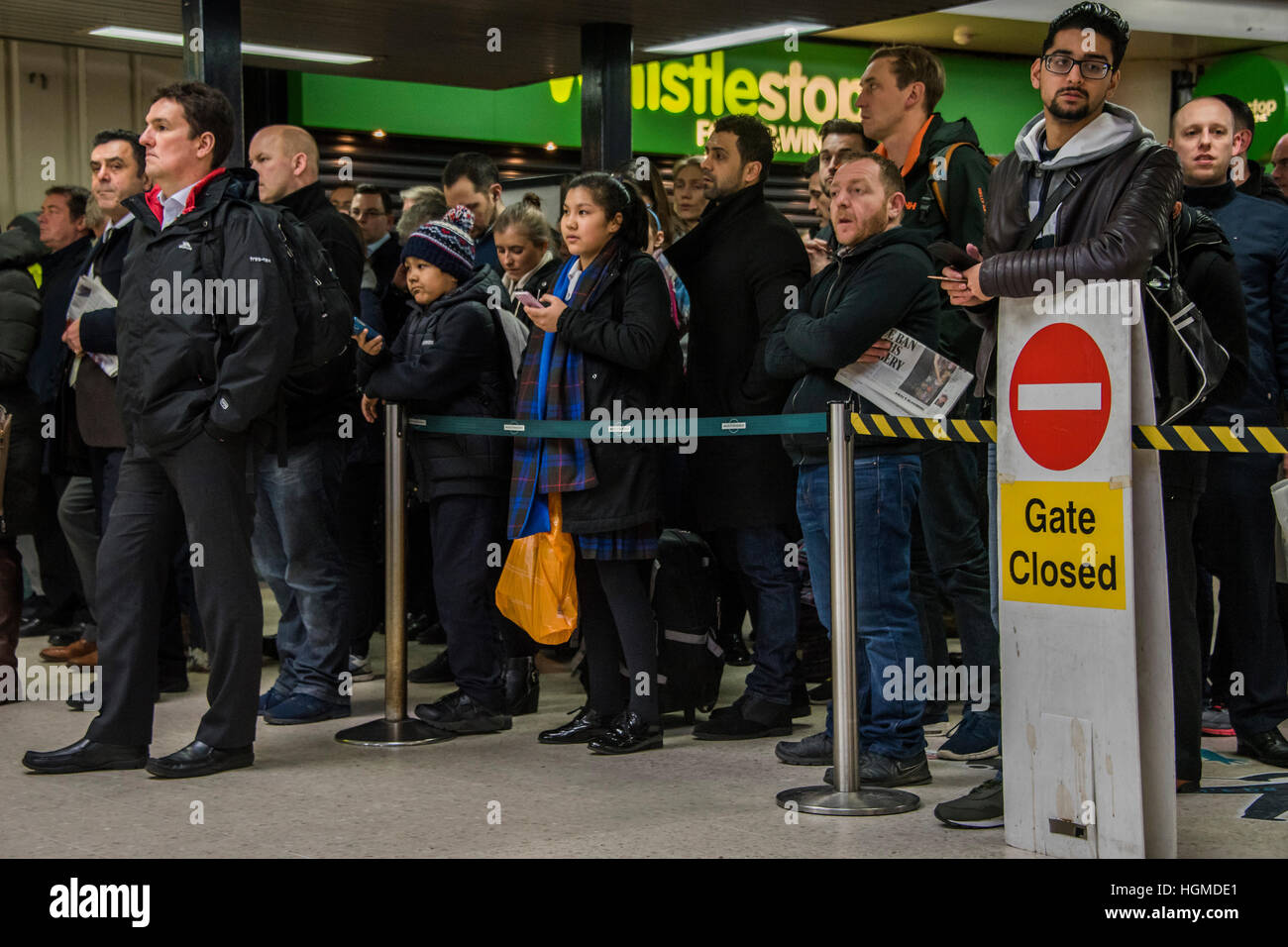 London, UK. 10th January, 2016. Passengers held behind barriers for 1 of four Caterham services tonight - Evening - Stock Image