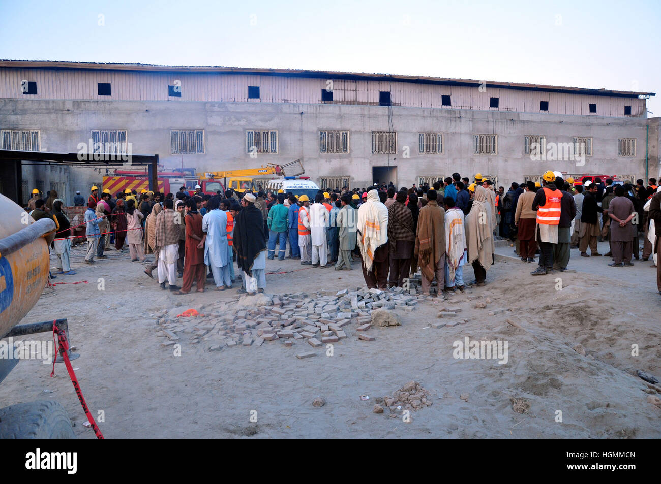 Lahore. 11th Jan, 2017. People gather outside the fire site in eastern Pakistan's Lahore on Jan. 11, 2017. At - Stock Image