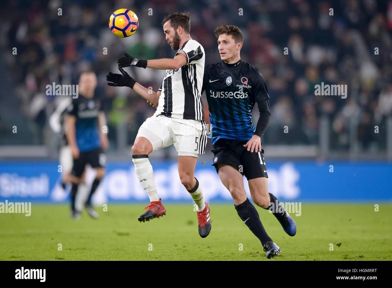 Turin, Italy. 2017, 11 January: Miralem Pjanic (left) of Juventus FC and Mattia Caldara of Atalanta BC compete for - Stock Image
