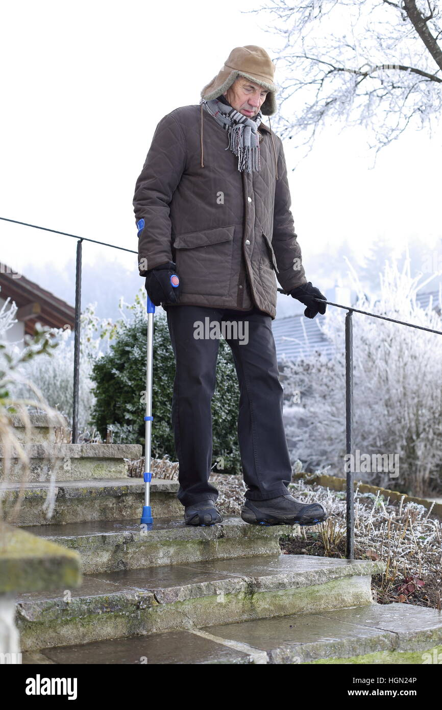 An Old man on crutches on icy stairs in winter - Stock Image