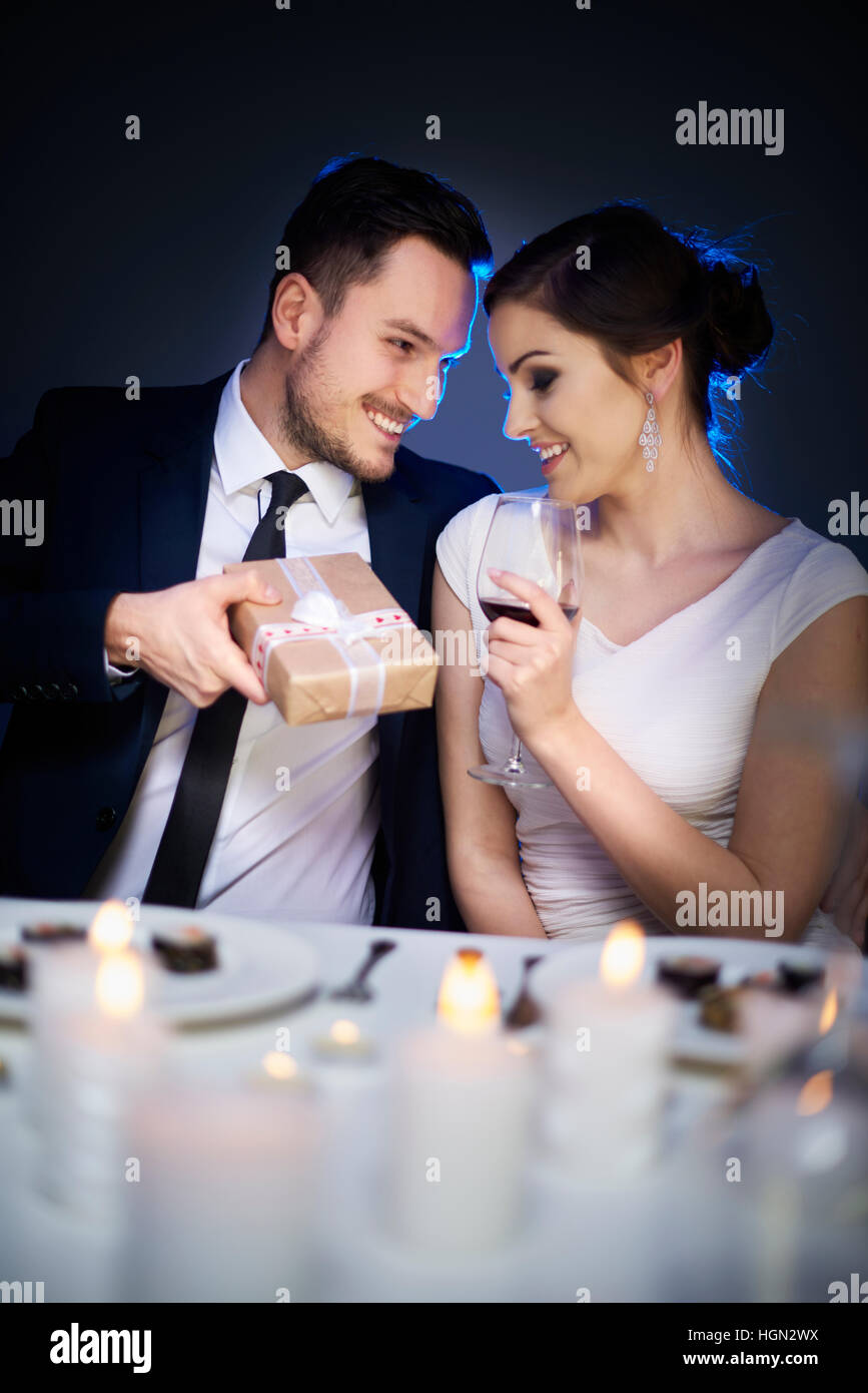 Handsome man bestowing woman with cute present - Stock Image