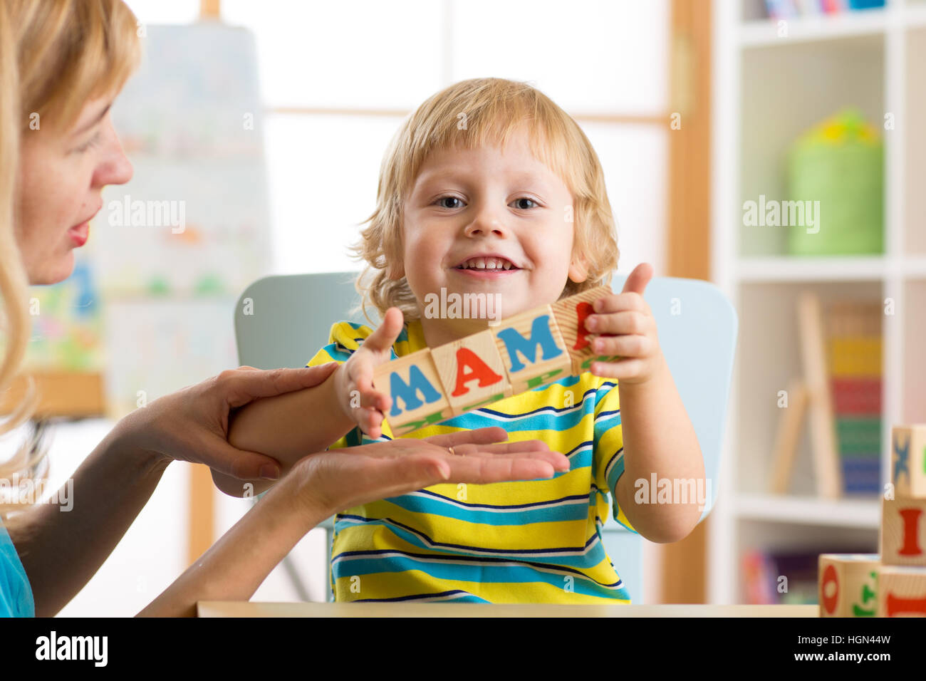 kid boy and mother building the word mama playing wooden cubes at home - Stock Image