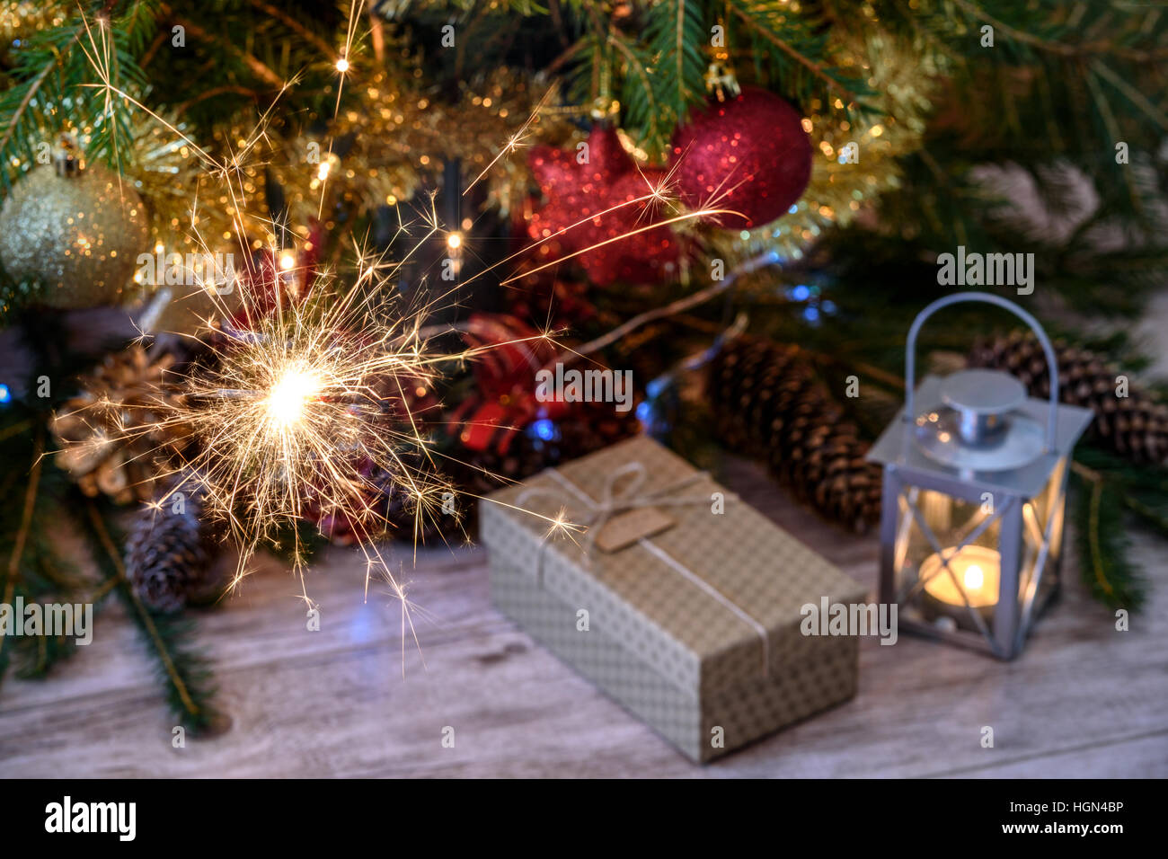 Sparklers and a gift with Christmas tree and lights - Stock Image