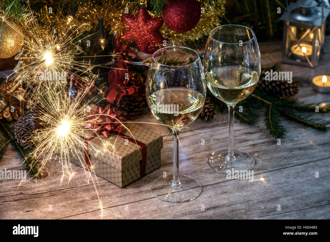 Sparklers at two wineglas with white wine on a wooden table in the background of Christmas tree, gift and candles - Stock Image